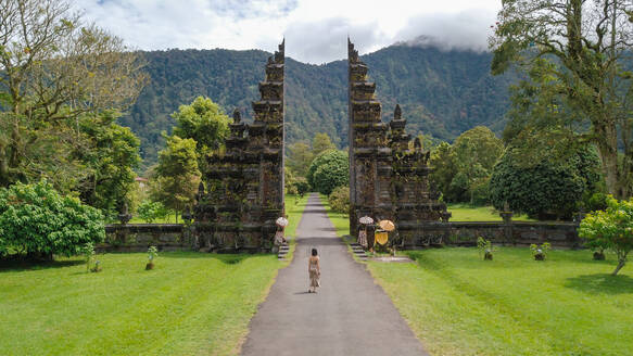 Aerial view of a woman in front of iconic Handara gate on a cloudy bright day in Bali, Indonesia - AAEF00646