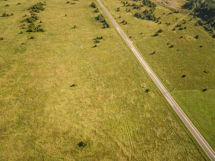 Aerial view of a en empty straight road in countryside of Estonia. - AAEF00928