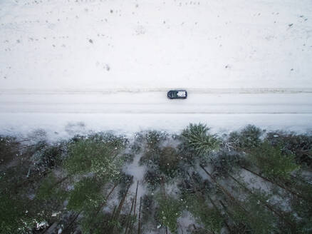 Aerial view of a car driving on snowy road in forest of Estonia. - AAEF00961