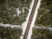 Aerial view of a car driving alone across a snowy forest in Estonia - AAEF01045