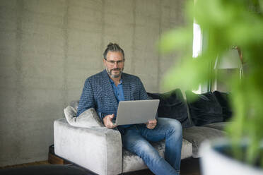 Portrait of mature businessman sitting on couch at home using laptop - MOEF02449