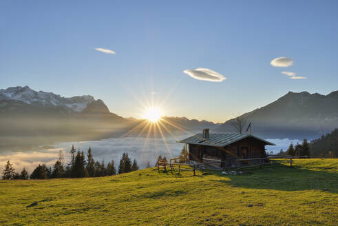 View of log cabin at Mt. Wank Zugspitze against cloudscape during sunset in Bavaria, Germany - RUEF02303