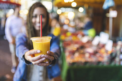 Woman's hands holding plastic cup of fresh orange juice, close-up - WPEF01682