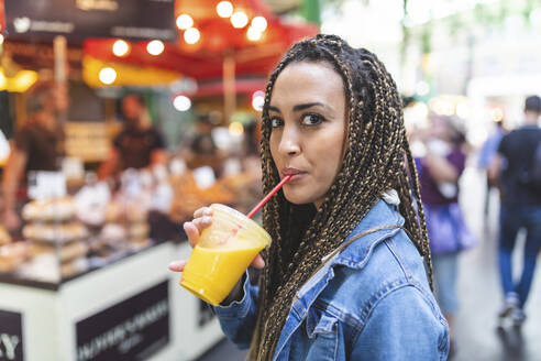 Portrait of young woman drinking fresh orange juice on street market, London, UK - WPEF01685