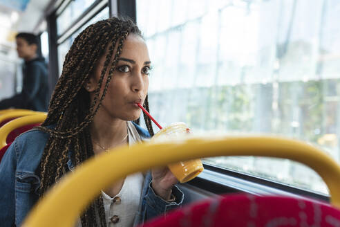 Young woman in a bus in the city drinking a fresh juice, London, UK - WPEF01688