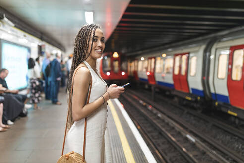 Portrait of smiling young woman with smartphone waiting at subway station platform, London, UK - WPEF01694
