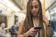 Portrait of young woman looking at cell phone in underground train, London, UK - WPEF01697