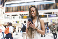 Portrait of happy young woman at train station using smartphone, London, UK - WPEF01700