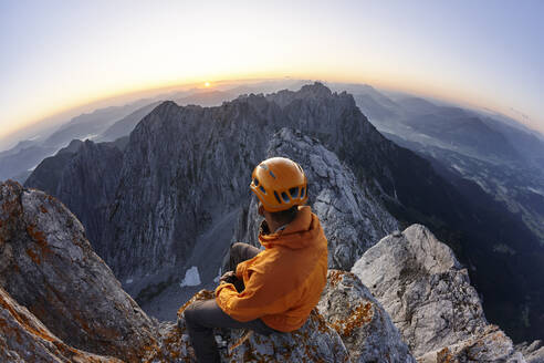 Climber with orange helmet sitting on Ellmauer Halt at sunrise, Wilder Kaiser, Ellmauer Halt, Tyrol, Austria - CVF01444