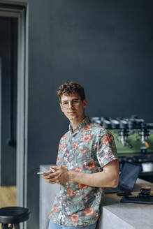 Young man standing in cafe, using smartphone - SODF00081