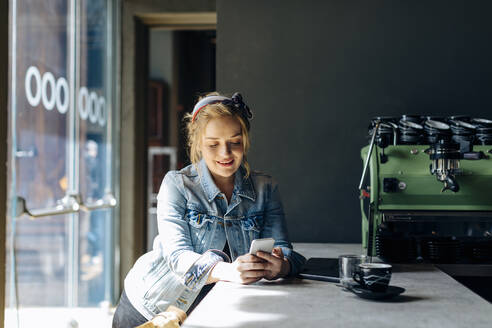 Young woman in coffee shop, using smartphone, taking pictures - SODF00084