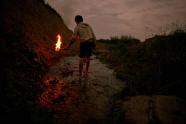 Mari man holding torch in rural creek - BLEF13822