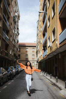 Asian woman walking on a road in Granada, Spain - LJF00618