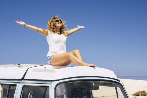 Woman sitting on the roof of a van, arms raised - SIPF02061