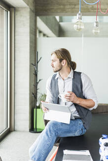 Young businessman sitting on table in office with tablet and cup of coffee - UUF18481