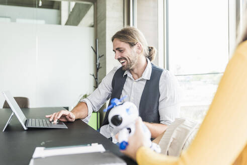 Happy young businessman and businesswoman sitting at desk in office - UUF18490