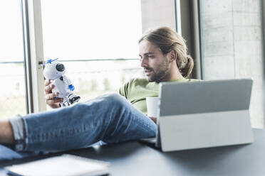 Young businessman sitting at desk in office holding robot - UUF18508