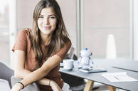 Portrait of smiling young businesswoman sitting at desk in office - UUF18511