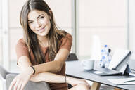 Portrait of smiling young businesswoman sitting at desk in office - UUF18514