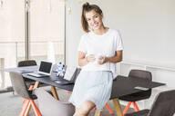 Portrait of smiling young businesswoman having coffee break in office - UUF18520