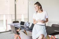 Smiling young businesswoman having coffee break in office - UUF18523