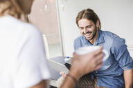 Laughing young businessman with laptop and businesswoman in office - UUF18532