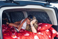 Pretty blond woman camping inside a van using tablet. - OCMF00560