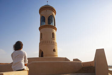 Rear view of man looking to Sur Lighthouse, Oman - WWF05157