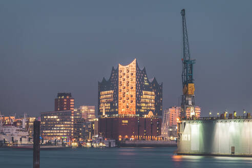 Illuminated Elbphilharmonie by Elbe River against sky in Hamburg at dusk, Germany - KEBF01278