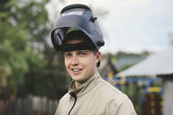 Portrait of smiling man with welding mask, standing in his backyard - EYAF00357