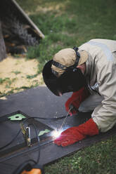 Man welding metal in his backyard - EYAF00360