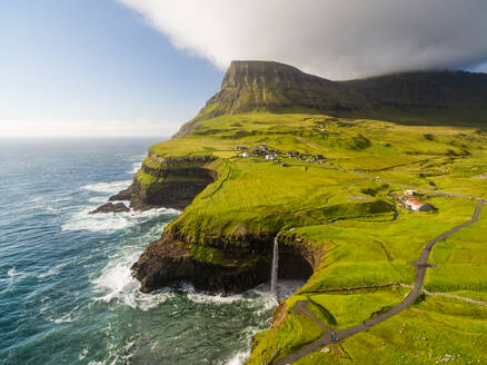 Aerial view faraway of Mulafossur waterfall near a small village, Faroe island - AAEF01329