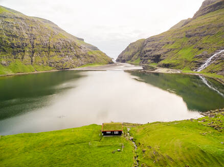 Aerial view of lonely house near a lake, Faroe island - AAEF01332