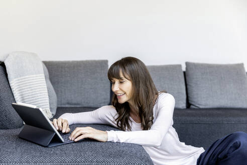 Relaxed woman using tablet in living room at home - FMKF05835