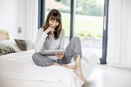 Happy woman with tablet sitting on bed at home - FMKF05844