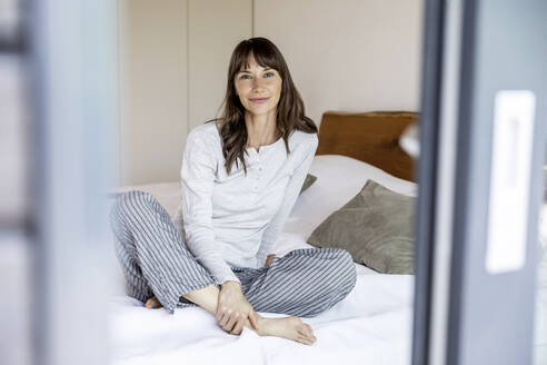 Relaxed woman sitting on bed at home - FMKF05847