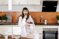 Portrait of woman wearing pyjama eating fruit in kitchen at home - FMKF05856