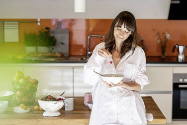 Portrait of woman wearing pyjama eating muesli with fruit in kitchen at home - FMKF05859