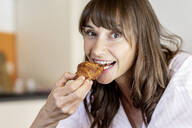 Portrait of happy woman eating a croissant - FMKF05862
