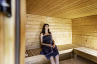Woman relaxing in a sauna - FMKF05865