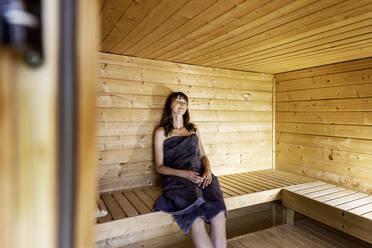 Woman relaxing in a sauna - FMKF05865