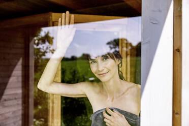 Portrait of smiling woman behind windowpane in a sauna - FMKF05871