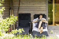 Woman relaxing on a lounge outside sauna using tablet - FMKF05874