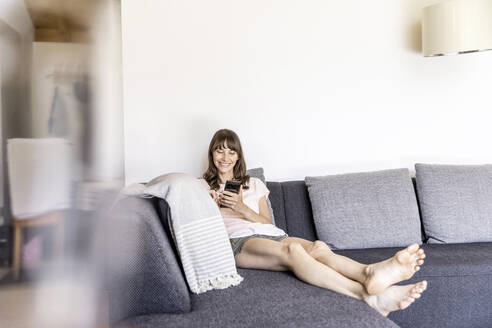 Relaxed woman using smartphone on couch at home - FMKF05880