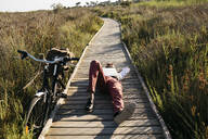 Well dressed man with laptop lying on a wooden walkway in the countryside next to a bike - JRFF03603