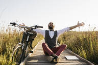Happy well dressed man sitting on a wooden walkway in the countryside next to a bike - JRFF03609