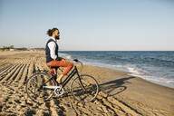 Well dressed man with his bike on a beach - JRFF03618