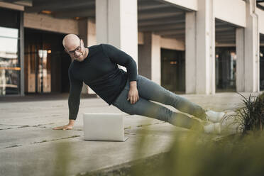 Portrait of smiling man doing pushups while looking at laptop - KNSF06207