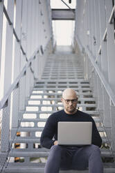 Portrait of bald man sitting on stairs using laptop - KNSF06213