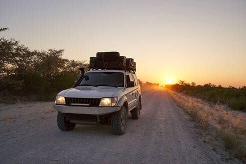 Off-road vehicle driving on a dirt road at sunrise, Makgadikgadi Pans, Botswana - VEGF00491